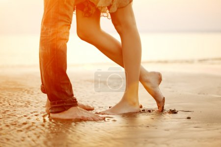 Photo for A young  loving  couple hugging and kissing on the beach at sunset. Two lovers, man and woman barefoot near the water. Summer in love - Royalty Free Image