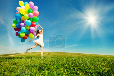 Photo for Happy birthday woman against the sky with rainbow-colored air balloons in hands. sunny and positive energy of nature. Young beautiful girl on the grass in the park. - Royalty Free Image