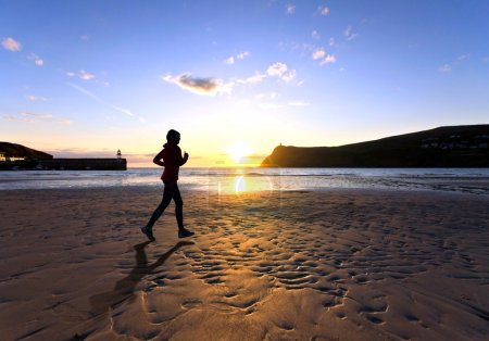 Woman running on a Beach during sunset
