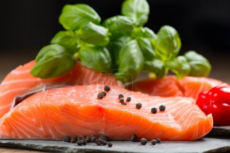 Photo pour Filet de saumon frais avec basilic et poivre sur des rochers plats - image libre de droit