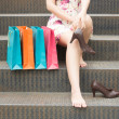 Girl Sitting On Stairs While Carrying Shoes In Han...