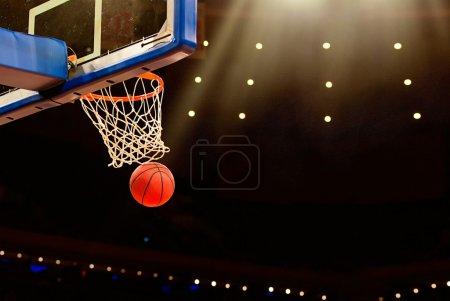 Photo pour Panier de basket avec ballon en passant par le net - image libre de droit