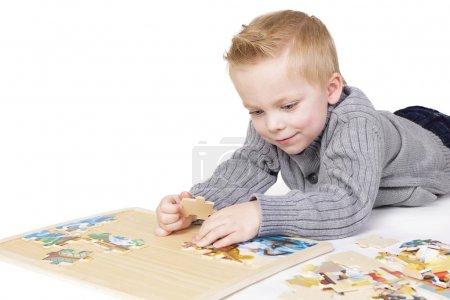 chico joven para resolver un rompecabezas
