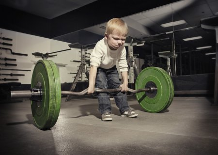 Photo for Determined young boy trying to lift a heavy weight bar - Royalty Free Image