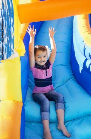 Little Girl sliding down an inflatable Slide