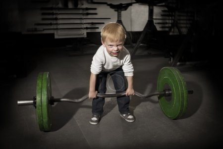 Photo for Determined Young Boy trying to lift Heavy weights - Royalty Free Image
