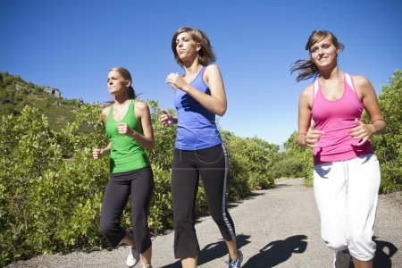 Photo pour Trois joggeuses qui courent ensemble à l'extérieur - image libre de droit