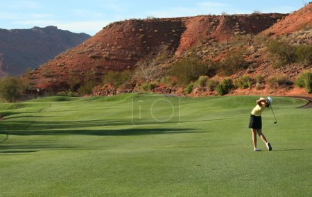 Woman playing golf on desert course