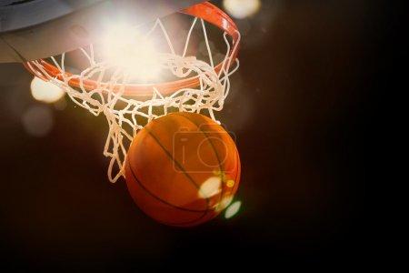 Photo pour Basket-ball en passant par le panier à un sports arena - image libre de droit