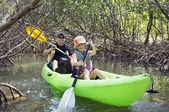 Family kayaking through forest