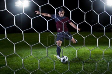 Photo pour Joueur de football hispanique prêt à tirer pendant un match. Vue de derrière le but. Jeu joué la nuit - image libre de droit