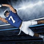 An american football player diving through the air...