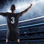 Hispanic soccer player raising his arms in celebra...