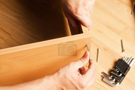 Carpenter mounting wooden furniture