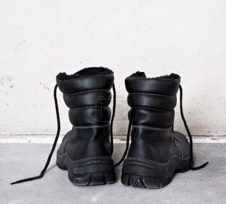 pair black worging boots on floor