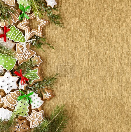 Photo for Christmas Ginger and Honey colorful cookies with fir tree branches and bows on the gold wrapping paper background. - Royalty Free Image