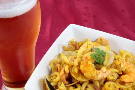 Photo for Partial view fideua bowl of seafood with beer on red tablecloth - Royalty Free Image