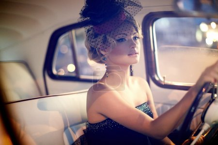 Beautiful sexy woman sitting in old car in retro style