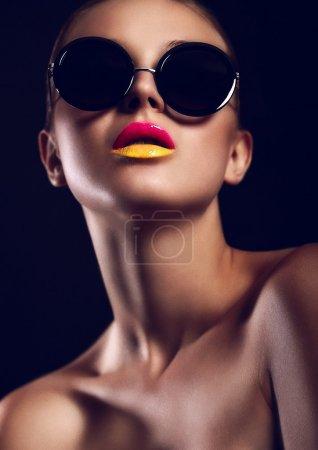 Photo pour Haute couture look.glamour gros plan portrait de sexy brune caucasienne jeune femme avec maquillage lumineux avec lèvres rouges et jaunes dans des lunettes de soleil - image libre de droit