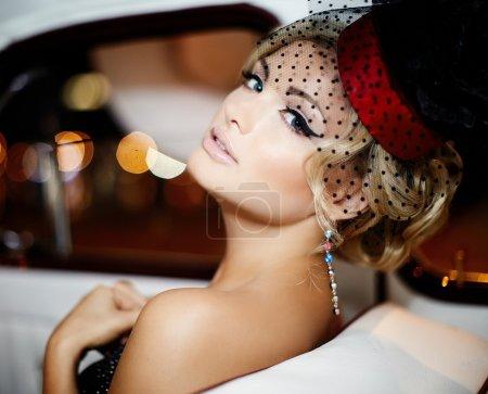 Photo pour Portrait de la belle sexy fille blonde élégante mannequin maquillage lumineux dans le style rétro, assis dans une voiture ancienne - image libre de droit