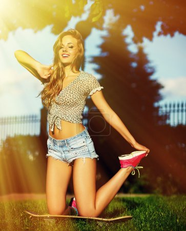 Sexy young stylish smiling woman girl model in bright modern cloth with perfect sunbathed body outdoors in the park in jeans shorts