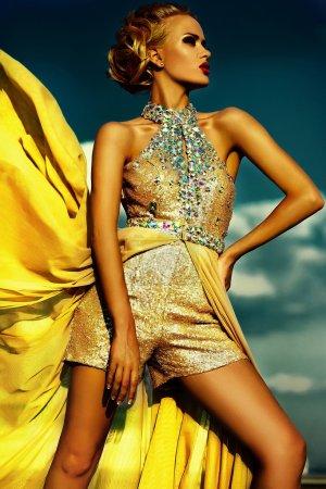 Photo pour Haute couture look.glamor belle sexy blonde élégante jeune femme modèle avec maquillage lumineux et lèvres rouges avec une peau propre privée parfaite avec bijoux à l'extérieur dans le style de vogue en robe de soirée jaune derrière bleu ciel - image libre de droit