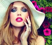 Vysoké módy look.glamor detailní portrét krásné sexy elegantní Mladá blondýnka model s světlý make-up a růžové rty s perfektní čistá kůže v hat blízko letní květiny