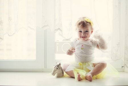 Photo for Smiling baby girl sitting near the window - Royalty Free Image