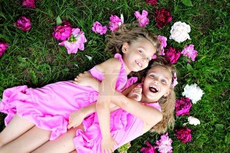 Foto de Retrato de dos gemelos con peonías - Imagen libre de derechos