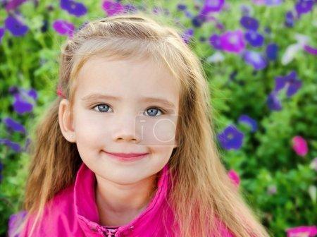 Outdoor portrait of cute little girl near the flowers