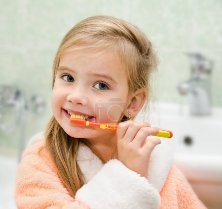 Photo pour Souriant petite fille brossant les dents dans le bain - image libre de droit