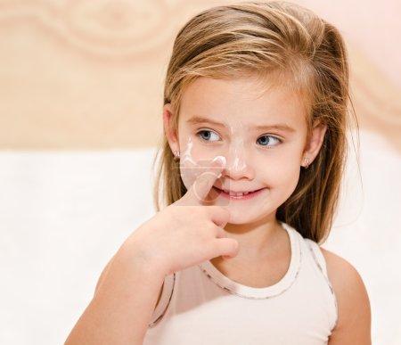 Cute little girl applying cream