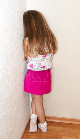Photo for Naughty little girl is standing in the corner at home - Royalty Free Image