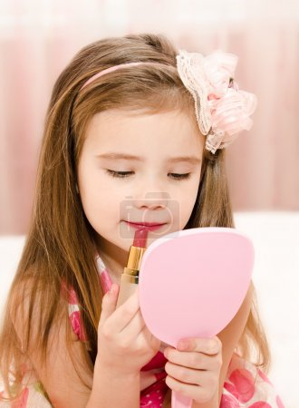 Photo for Cute little girl with lipstick and  mirror - Royalty Free Image