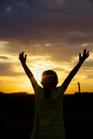 Girl enjoying a beautiful sunset holding his hands to the sky to thank God