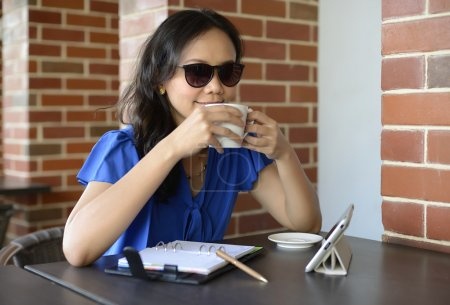 Happy woman with sunglasses drink in Cafe