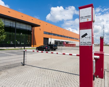 Photo for Secured entrance of a modern orange warehouse in the Rotterdam harbor area - Royalty Free Image