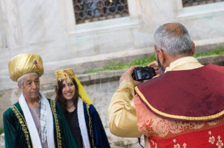 Photo pour Homme turc traditionnel prenant des photos de certains touristes habillés. Istanbul est l'un des lieux touristiques les plus importants non seulement en Turquie, mais aussi dans le monde . - image libre de droit