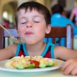 Cute little boy enjoying food. Child eating pasta with vegetables