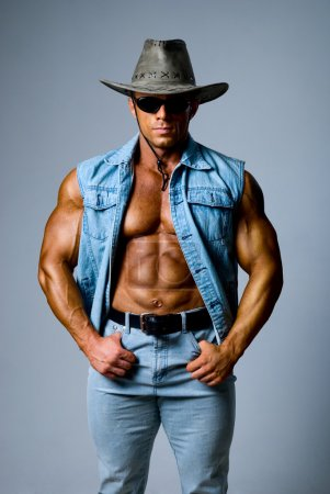 Photo for Muscular man in a cowboy hat on a gray background - Royalty Free Image