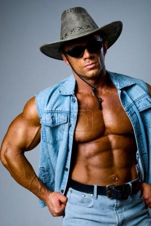 Handsome muscular man in a cowboy hat