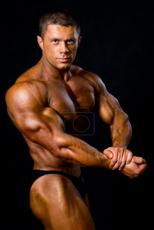 Handsome muscular bodybuilder in studio