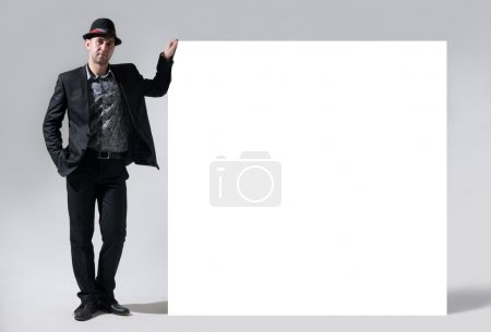 A man in a hat stands next to a blank billboard