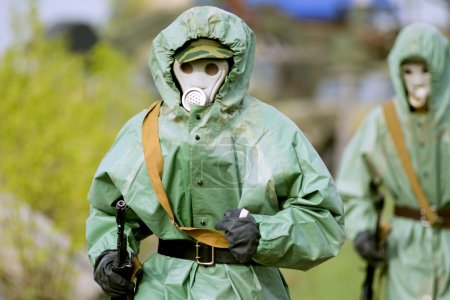 Photo for Military man in protective suit and gas mask outdoors. Are holding an automatic weapon - Royalty Free Image