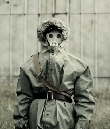 Military man in protective suit and gas mask outdoors
