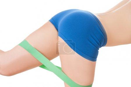 Photo pour Fittness femme exerçant avec bande de caoutchouc greenelastic porter des shorts d'entraînement bleu - image libre de droit