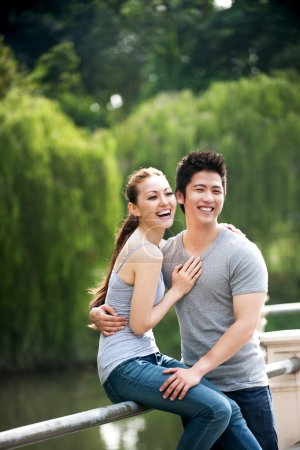 Asian couple sitting on embankment in the park