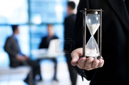 Close up of businessman hand holding hourglass.