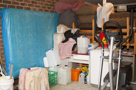 Photo for Suburban garage used as self storage full of household items and mess - Royalty Free Image