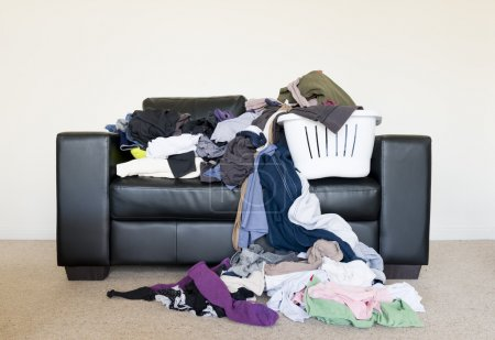 Photo for Housework concept of a large pile of laundry dumped on the couch, waiting to be folded and put away - Royalty Free Image